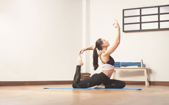Long haired beautiful pilates or yoga athlete does a graceful stretching pose with while wearing a tight sports outfit  in a yoga studio