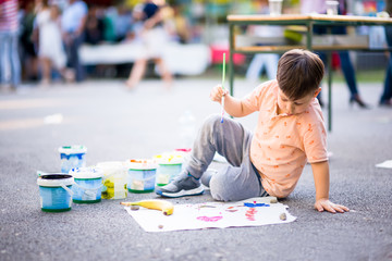 Boy using a paintbrush to paint a sheet of paper