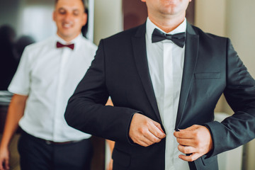 Stylish handsome groom posing while groomsman putting on shirt and tying bow, helping him to get ready in the morning. wedding preparation.
