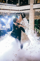 First wedding dance of newlywed. Amazing dancing bride and groom on low light and heavy smoke.  A lot of confetti.