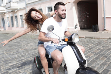 Happy young couple having fun on a scooter