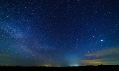 Starry sky and illuminated clouds. Bright star-planet Jupiter.