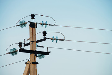 Power lines on background of blue sky close-up. Electric hub on pole. Electricity equipment with copy space. Wires of high voltage in sky. Electricity industry.