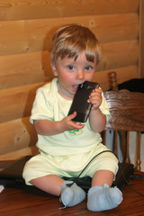 baby infant boy sits on a Desk on a laptop and holds a cell phone in his mouth