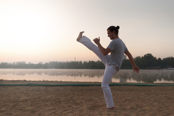 Capoeira on the beach, near lake in the park one performer, at s