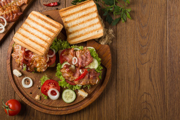 Toasted sandwich with bacon, tomato, cucumber and lettuce.