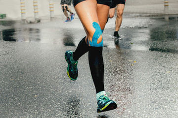 Fototapete - legs runner woman with kinesio tape and compression socks