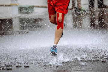 Wall Mural - athlete runner knee kinesio tape running water splashes and drops