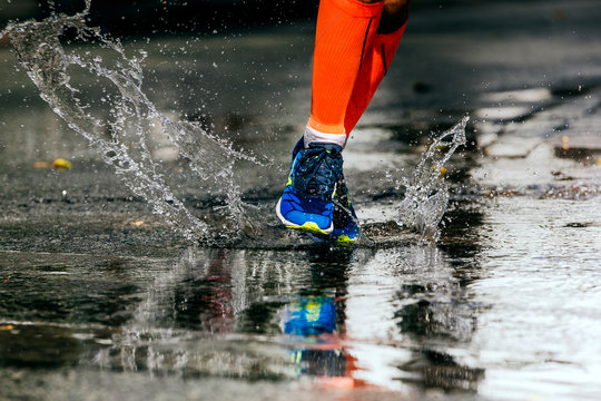 athlete runner run on puddle splashes and drops of water