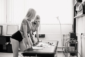Girls twins with blonde hair in short shorts choose sketches for tattoo, black and white photo