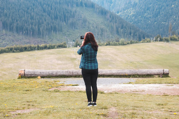 A young girl in a blue green shirt stands in a meadow and takes pictures of mountains covered with pine forest with her mobile phone