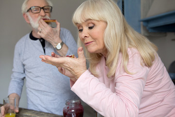 Elderly married couple enjoying their snack. Charming old lady with blond hair eating bread with jelly with her husband in background.