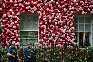 Armed police officers walk past Annabel's private members club, adorned with thousands of flowers, timed to coincide with the RHS Chelsea Flower Show, as they patrol in Mayfair in London, Britain