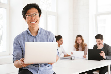 Happy young asian man holding laptop