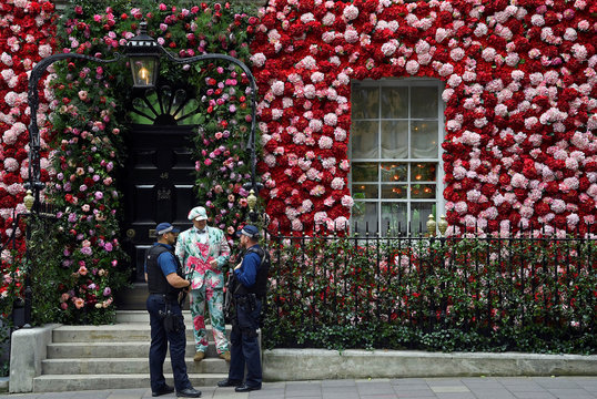 A doorman dressed in floral pattern suit speaks to armed police officers as he stands on duty outside of Annabel's private members club, adorned with thousands of flowers, timed to coincide with the RHS Chelsea Flower Show, in Mayfair in London, Britain