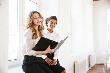 Two smiling business women sitting indoors