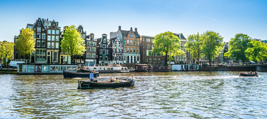 Papiers peints Amsterdam Amsterdam, May 7 2018 - view on the river Amstel filled with small boats and traditional houses in the background on a summer day