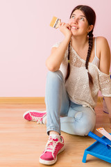 Photo of young woman with paint roller sitting on floor