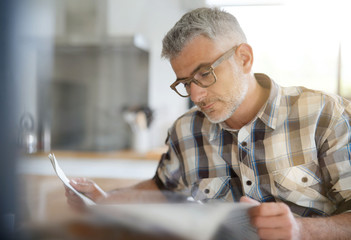 Middle-aged man in kitchen reading newspaper