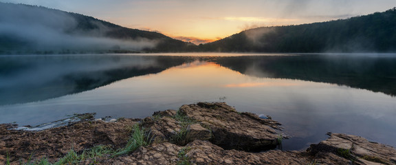 French landscape - Jura. View over the lake of Narlay in the Jura mountains (France) at sunrise with rocks in the foreground.
