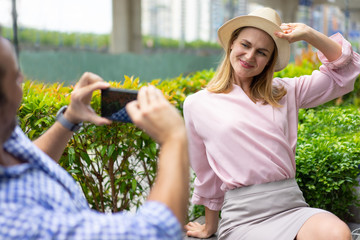 Happy elegant young woman wearing hat posing for photo in park