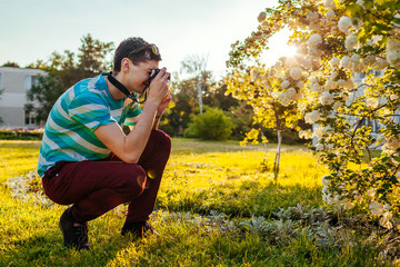 Man photographer taking pictures of flowers in park at sunset. Young guy enjoys his hobby outside.