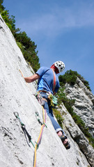mountain guide climbing a steep slab pitch of a hard rock climbing route in the Alps of Switzerland
