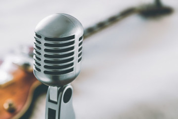 etro microphone on blurred background with electric guitar lying on white blanket