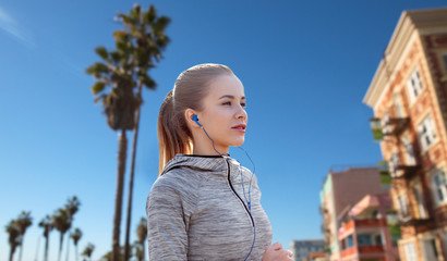 fitness, sport and technology concept - happy woman running and listening to music in earphones over venice beach background in california