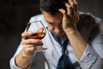 alcoholism, alcohol addiction and people concept - close up of male alcoholic drinking brandy at night