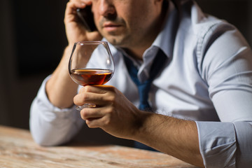 alcoholism, alcohol addiction and people concept - close up of male alcoholic drinking brandy and calling on smartphone at night