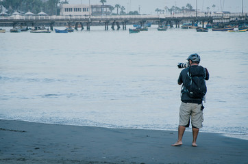 Young photographer with his professional camera taking pictures of boats in the sea
