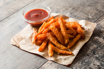 Sweet potato fries and ketchup sauce on wooden table