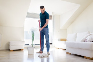 household, housework and people concept - happy man with mop and bucket cleaning floor at home