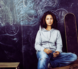 young cute teenage girl in classroom at blackboard seating on table smiling, modern hipster concept