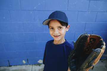 Portrait of smiling boy wearing baseball glove while standing against blue wall