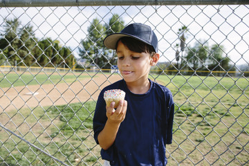 Boy eating cupcake while standing by chainlink fence at playing field