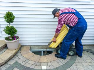 Man doing maintenance on a basement window