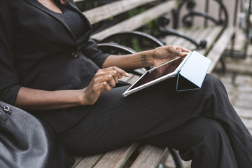 Midsection of businesswoman using tablet computer while sitting on bench in city