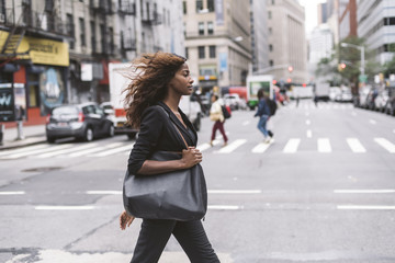 Side view of confident businesswoman walking on city street