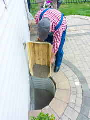 Man replacing the old pebbles in an egress window