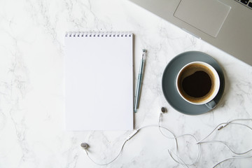 Workplace flatlay with notebook, laptop and coffee cup on marble table
