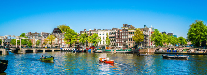 Aluminium Prints Amsterdam Amsterdam, May 7 2018 - view on the river Amstel filled with small boats and the Magere brug (skinny bridge) in the background on a summer day