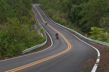 Beautiful mountain asphalt road with curve and double yellow line with two bikers riding motorbike, moto trip in north thailand