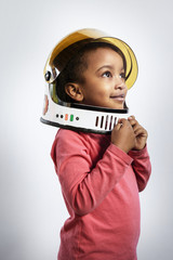 Thoughtful preschool girl wearing space helmet