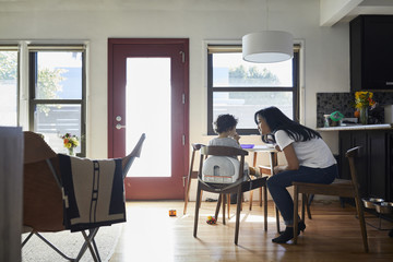 Side view of mother talking with son sitting on chair in living room at home