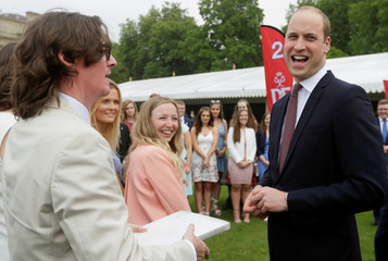 Britain's Prince William laughs as he meets comedian Ed Byrne during a day of DofE presentations at Buckingham Palace in London