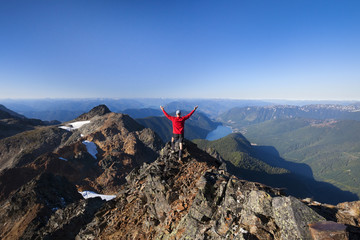 Rear view of hiker with arms raised standing on mountain against clear sky