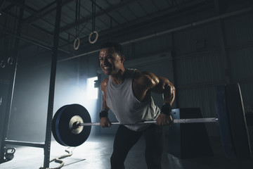 Low angle view of male athlete lifting barbell in gym