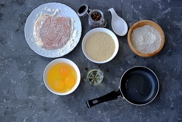 Prepared ingredients for pork chops. Meat, bread crumbs, wheat flour, eggs, salt, pepper, frying pan and frying oil